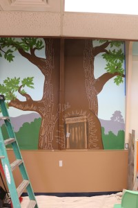 Close up of Mr. Saunders (aka Winnie the Pooh) reading tree mural with Nancy's highlight sketch